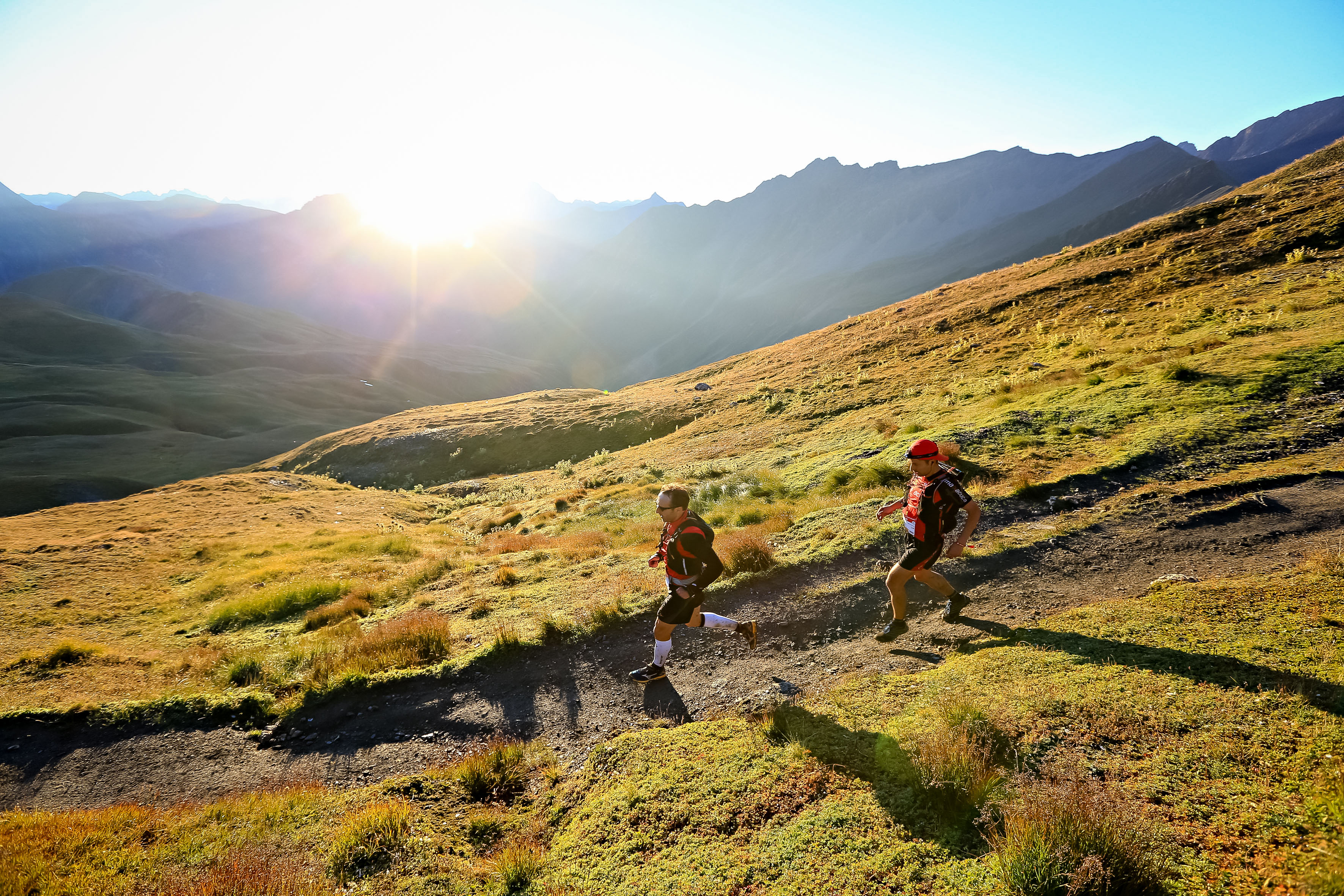 Trail runners in front of sun in the mountains