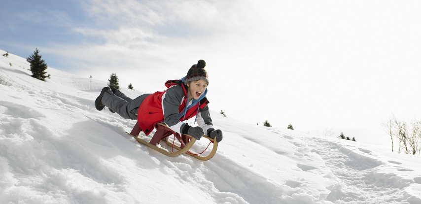 Boy On A Sled Playing In The Snow